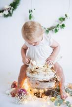 Toddler Girl Sitting On Cake