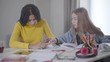 Portrait of intelligent female students sitting with notebooks and talking. African American and Caucasian girls studying together. Blond teen looking into friend's notes. Education, lifestyle.