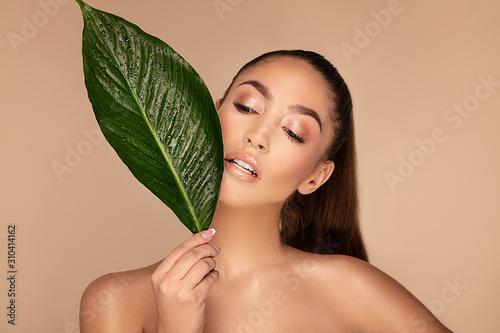 Fototapeta Beautiful brunette woman with green leaf. obraz