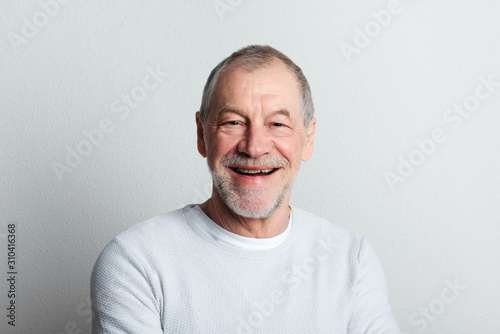 Photo Portrait of a cheerful senior man with beard and mustache in a studio