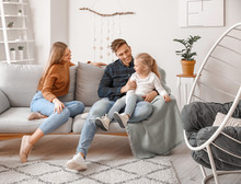 Happy Young Family Sitting On Sofa At Home
