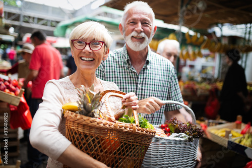 Fotomural Mature couple shopping vegetables and fruits on the market