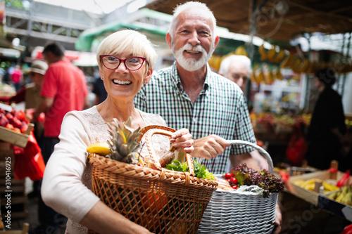 Fototapeta  Mature couple shopping vegetables and fruits on the market