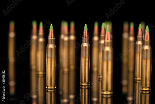 Photo A group of 5.56 calibar, green tip bullets on black background