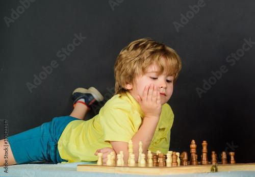 Cute little boy playing chess enjoying leisure time Wallpaper Mural