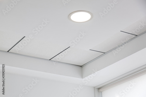 Canvas Print multi-level ceiling with three-dimensional protrusions and a suspended tiled ceiling with a built-in round led light