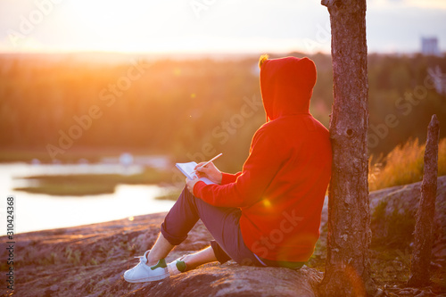 Man in hoodie writing in notebook, sitting on top of the rock Canvas Print