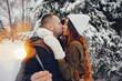 Pretty couple walking in a winter park. Man and woman have fun with snow