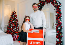 Funny Little Girl And Her Father In Red Eyeglasses Stands Near Mailbox Indoors.