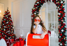 Funny Child Girl Is Standing Near Red Christmas Mailbox And Sends A Letter To Santa Claus.