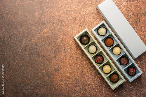 Fotomural Handmade chocolates in different boxes on a dark background