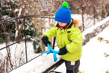 Child Plays With Snow Outdoors...