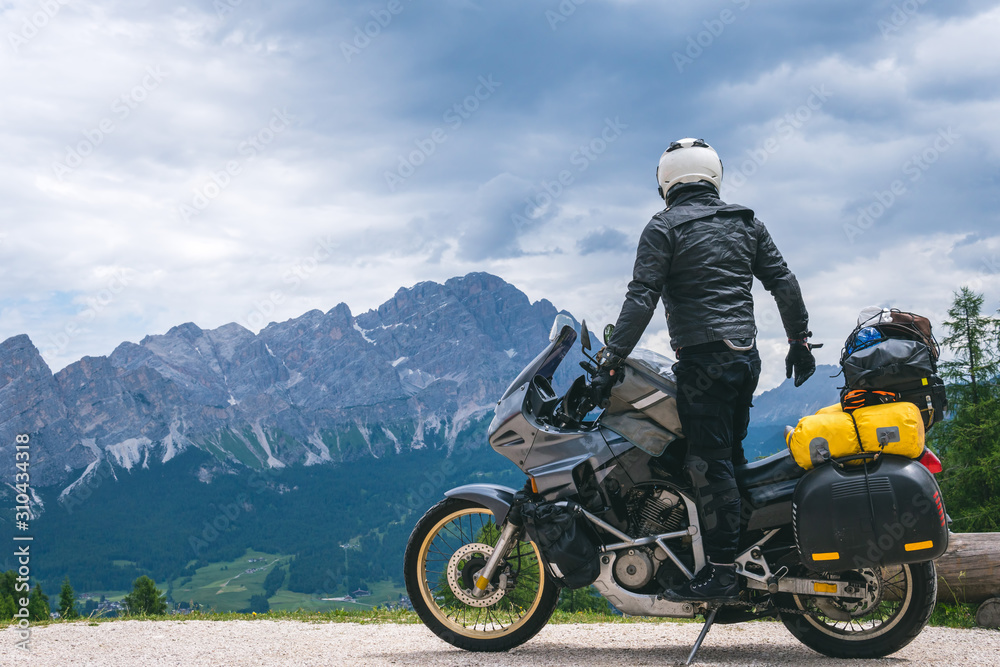 Fototapeta Back view of stylish biker on adventure touring motorcycle in full equipment on dirt road, Look at distance on top of Dolomites mountains, travel concept, copy space. Cortina Ampezzo, Italy