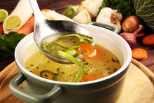 Broth With Carrots, Onions Various Fresh Vegetables In A Pot - Colorful Fresh Clear Spring Soup. Rural Kitchen Scenery Vegetarian Bouillon Stock