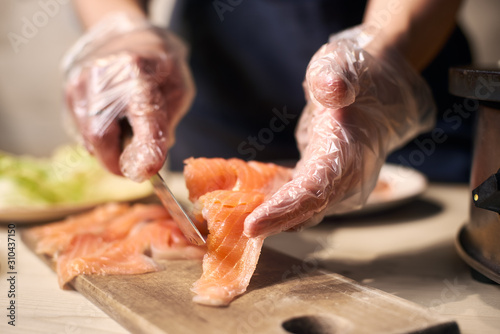 Focus on process of slicing with knife pieces of fish on cutting board for cooking food Canvas Print