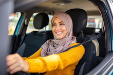 Portrait Of Muslim Asian Young Woman Driving Her Car. Arab Women Driving Car. Middle Eastern Woman Driving A Car, Looking Forward. Get Driving License Concept