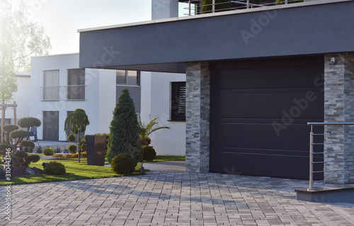 Obraz Garage of a modern European house with an automatic door next to garden plants - fototapety do salonu