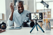 Charming young African man in shirt showing digital camera and telling something while making social media video