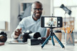 Happy young African man in shirt showing digital camera and telling something while making social media video