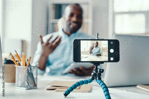Handsome young African man in shirt telling something and smiling while making social media video