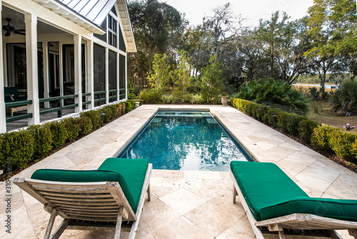 Fototapeta Beautiful back yard pool behind luxury home with garden obraz