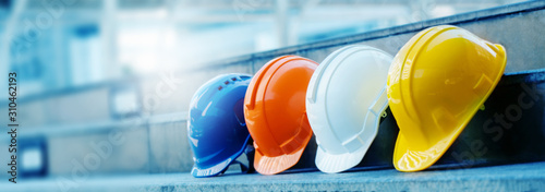 Obraz Multicolored Safety Construction Worker Hats. Teamwork of the construction team must have quality. Whether it is engineering, construction workers. Have a helmet to wear at work. For safety at work. - fototapety do salonu