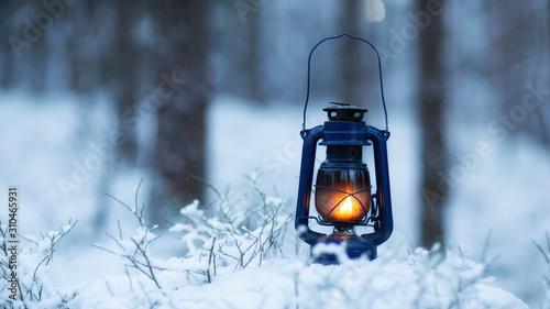 Mystical scene with old kerosene lamp in snow Fototapete