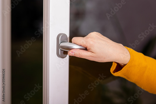 Photo Woman opens the window to ventilate
