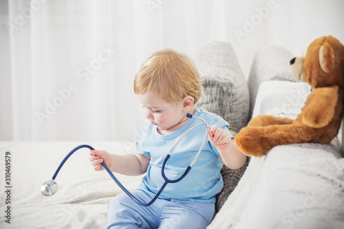 plakat little child plays doctor with teddy bear at home