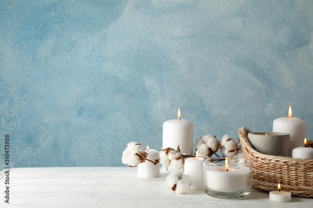 Fototapeta Burning candles, basket and cotton on white wooden table, space for text