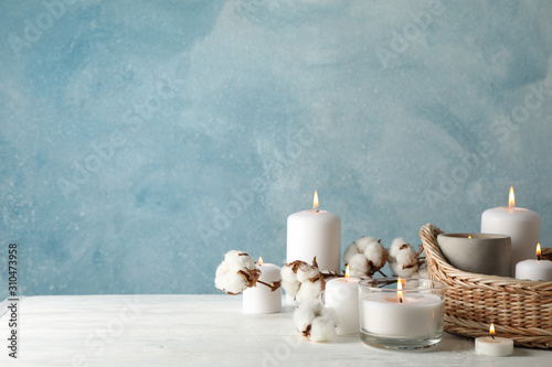 Obraz Burning candles, basket and cotton on white wooden table, space for text - fototapety do salonu