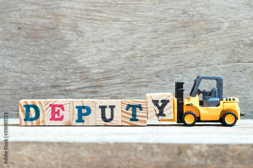 Fotografia, Obraz Toy forklift hold letter block y to complete word deputy on wood background