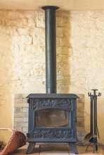 Cast Iron Wood Burning Stove And Tools In The Rustic Home Interior. Vertical Picture