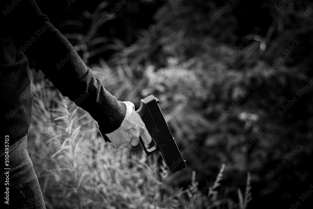 Fototapeta woman holding a gun in hand. - violence and crime concept.