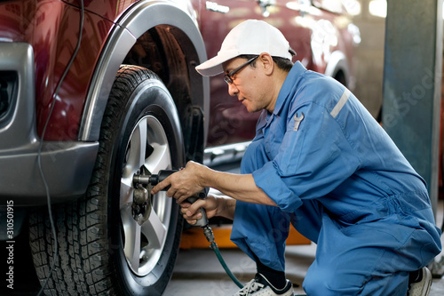 Fotografía  Asian automotive mechanic with white cap and blue uniform is working with replace or fix the problem of car wheel in the garage