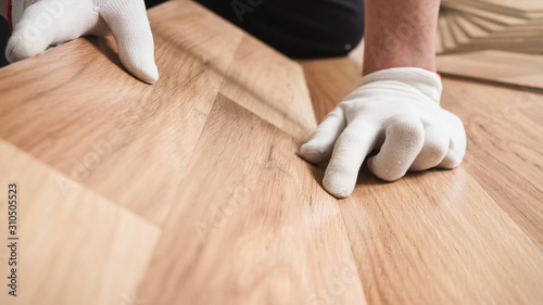 Photo Installing laminated floor, detail on man hands in white gloves fitting wooden t