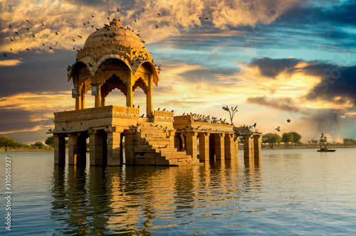 Sandstone chattri domes with steps on gadi sagar lake in jaisalmer at dusk Fototapete