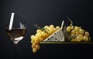 Glass of white wine with snacks. Grapes with blue cheese and thyme.