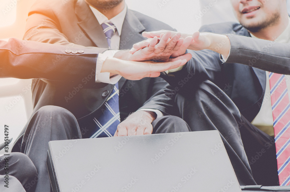 Fototapeta group of business people joining their hands together in unity with successful