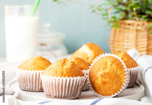Freshly baked homemade muffins in white paper muffin cups and a glass of milk on the table Obraz na płótnie