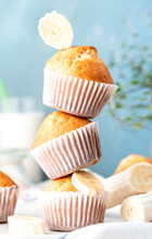 Stack Of Banana Muffins In White Paper Muffin Cups Close-up, Blue Background. Homemade Sweet Pastries, Delicious Sweet Breakfast.