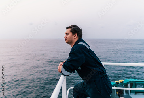 Leinwand Poster Marine Deck Officer or Chief mate on deck of offshore vessel or ship , wearing PPE personal protective equipment - helmet, coverall