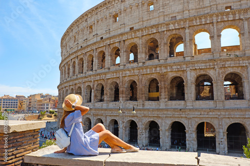 Photo Travel woman in romantic dress and hat sitting and looking on Coliseum, Rome, Italy