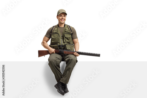Tableau sur Toile Young man hunter with a rifle sitting on a blank board