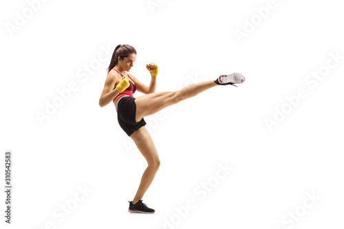 Photo  Young fit woman kicking with a leg