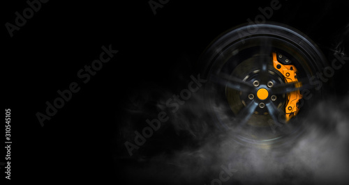 Isolated generic sport car wheel with yellow breaks drifting and smoking on a black background - 310545105