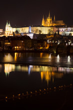 Night Winter Prague Lesser Town With The Gothic Castle And Charles Bridge Above The River Vltava, Czech Republic