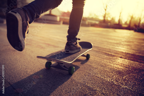 Valokuvatapetti Skateboarder skateboarding at sunrise city