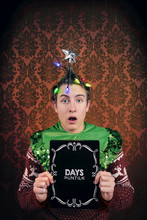 """Teenage Boy With Christmas Tree Shaped With Lights Holding A Sign With """"days Until"""" On It"""