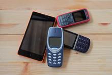 Old Used Mobile Phones On Wood...